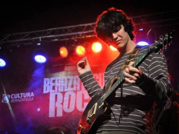 La imagen puede contener: 1 persona, tocando un instrumento musical, en el escenario, guitarra y noche